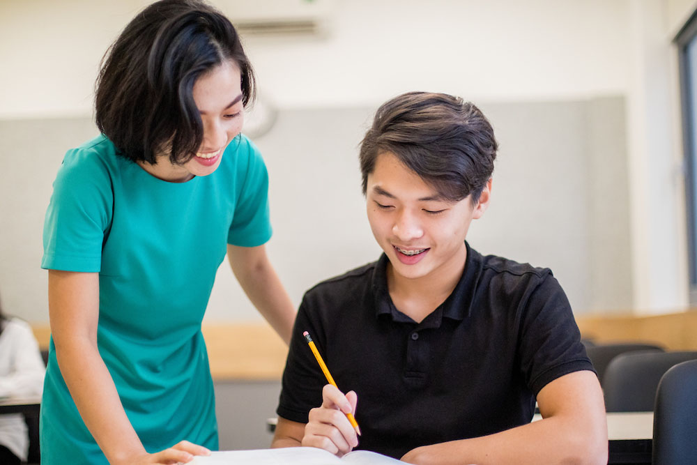 tutoring-high-school-asian-student-with-teacher